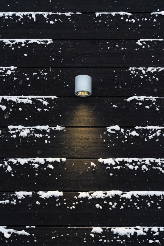 Fasaden är klädd i liggande limträpanel och är behandlad med svart slamfärg.