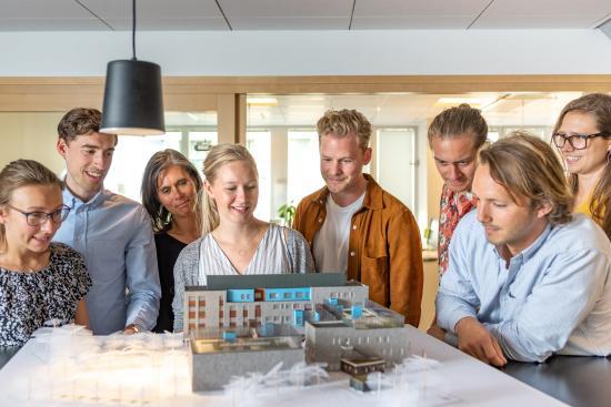 En fysisk modell av Västra Varvstaden tillsammans med de konstruktörer och arkitekter som arbetat med projektet genom ett integrerat arbetssätt.