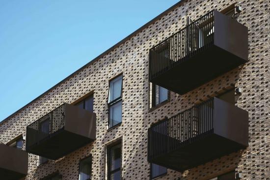 """Inspirationen till våningsbygget """"Iris Hus"""" i Köpenhamns gröna stadsdel har hämtats från den norditalienska staden San Gimignano, där takspiror och tunga tegelblock uppgår i symbios runt den sydeuropeiska stadens inre rum."""