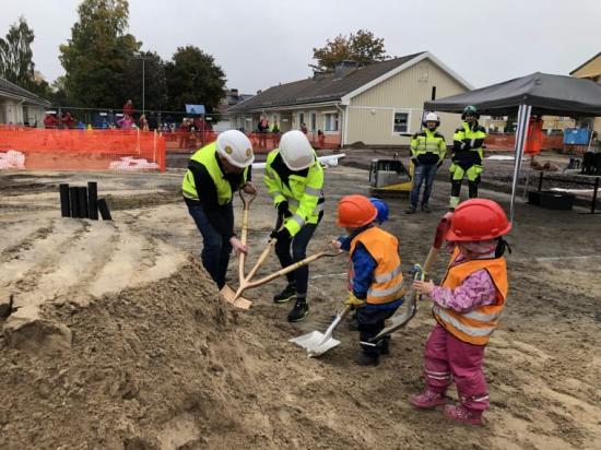 Ordförande i teknik- och fastighetsnämnden Henrik Lander (C) och projektledare Charlotte Stenberg får grävhjälp av några av barnen på Norrstrands förskola.