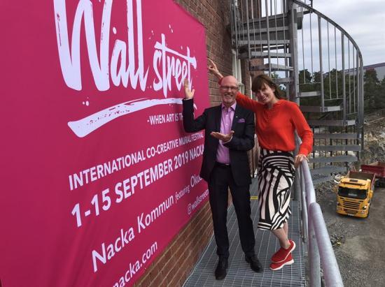 Mats Gerdau, kommunstyrelsens ordförande, och Fredrika Friberg, stadskreatör, vid väggen på Nacka stadshus som ska prydas av en muralmålning.